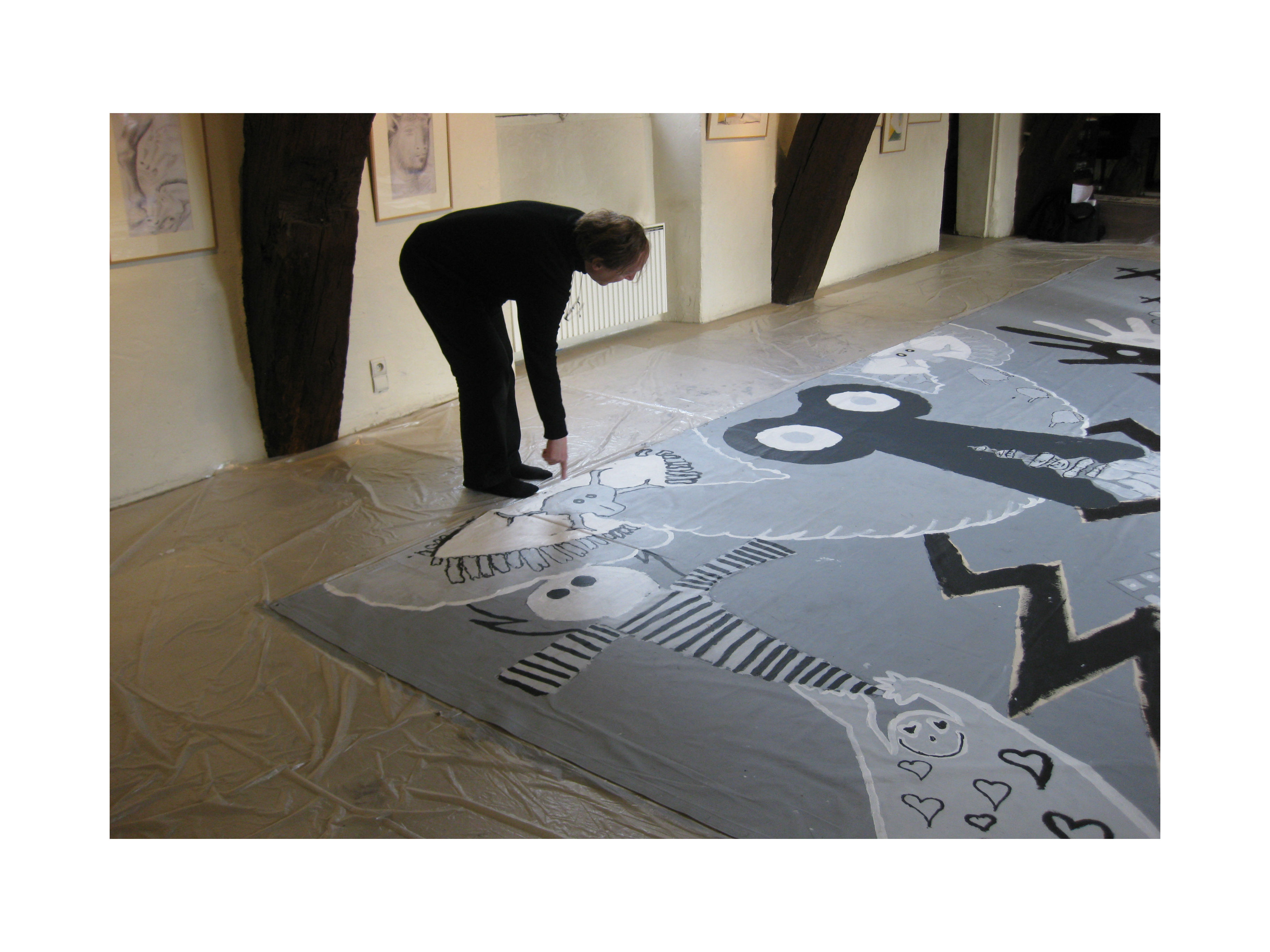Staging the black and white mural create on the canvas can be seen white sheets of paper which contained sketches of children they were selected and meant to be drawn and then painted onto the buycottarizona Gallery